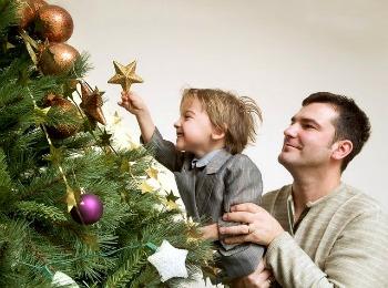 Папа с сыном украшают ёлку