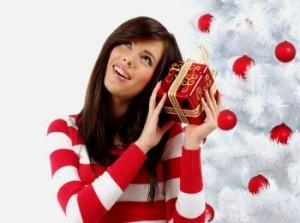 Девушка с новогодним подарком у елки