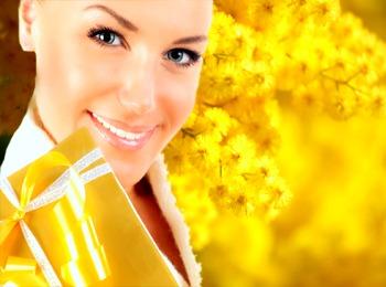 Девушка с подарком на фоне цветов мимозы