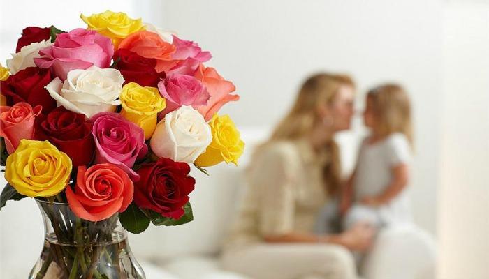 Мама с дочкой на фоне букета роз